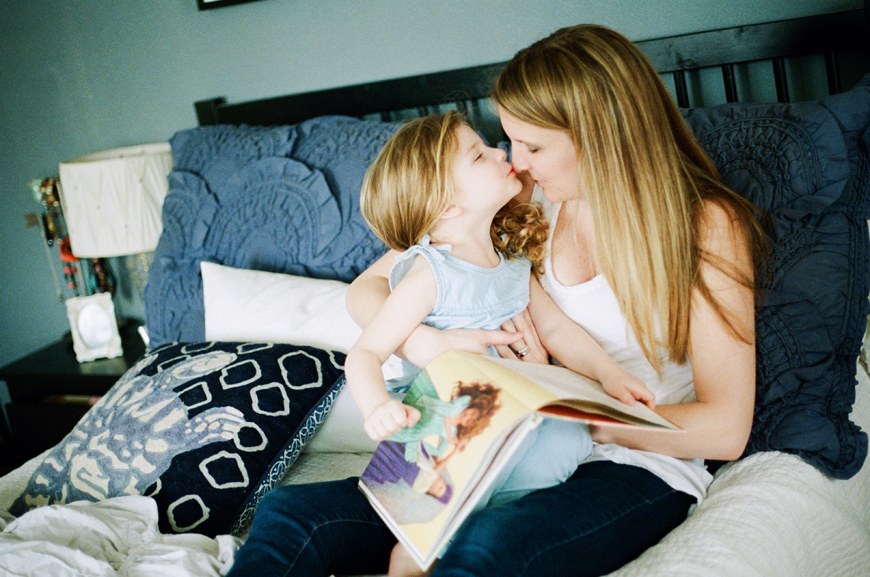 little girl kissing mom reading book photo