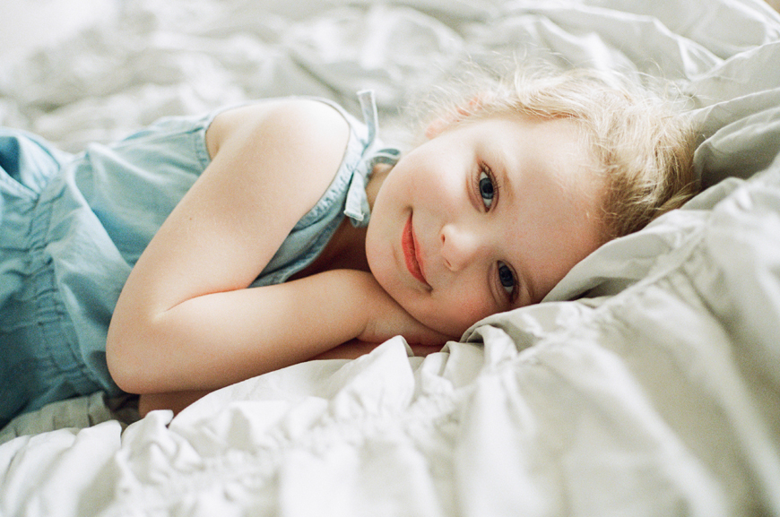 little girl laying down on bed image by lalee photography
