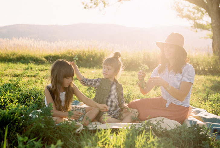 little girls putting flowers in hair in grass by green apple photography