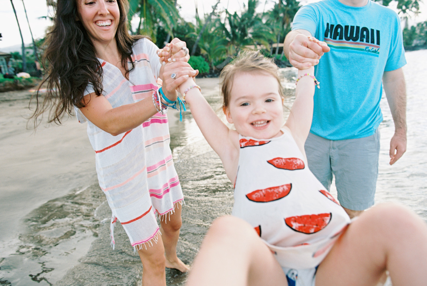 little girl in watermelon dress swinging with parents image
