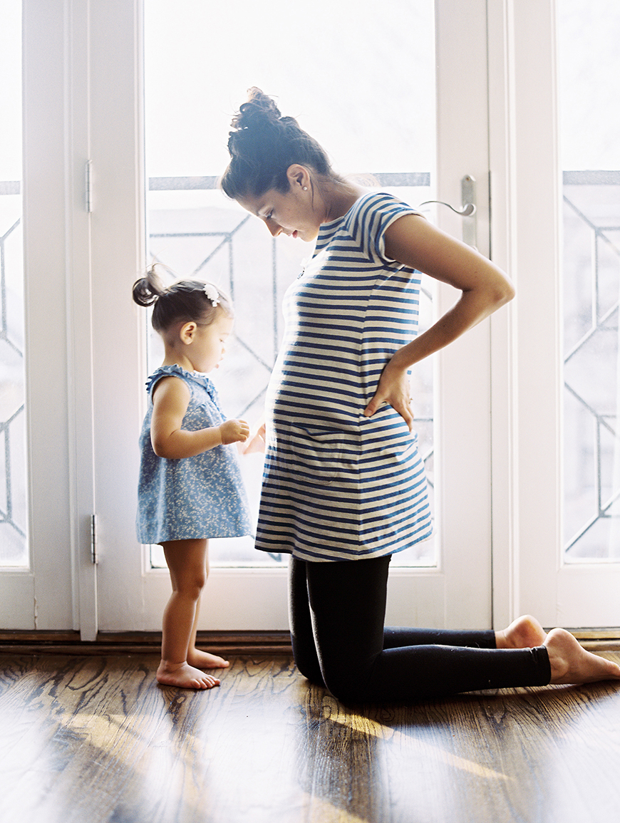 photo of mom in stripes with daughter facing each other in window light by photographer momoko fritz