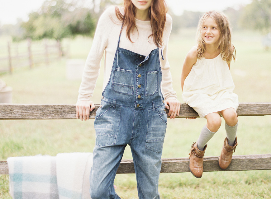 photographer heather hawkin's image of mom in overalls and daughter in white sitting on fence