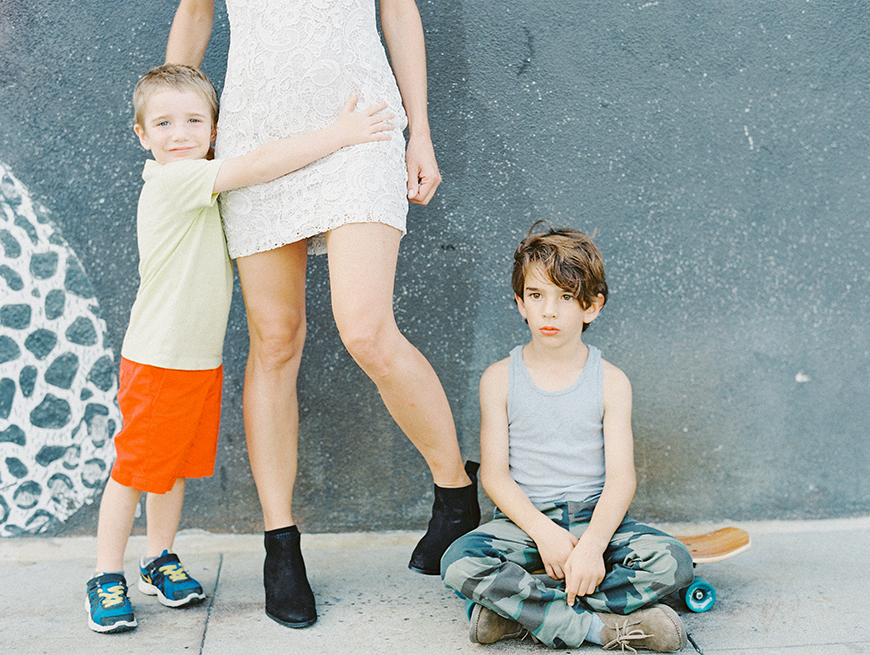 two little boys holding moms legs against grey wall in la by darcy benincosa