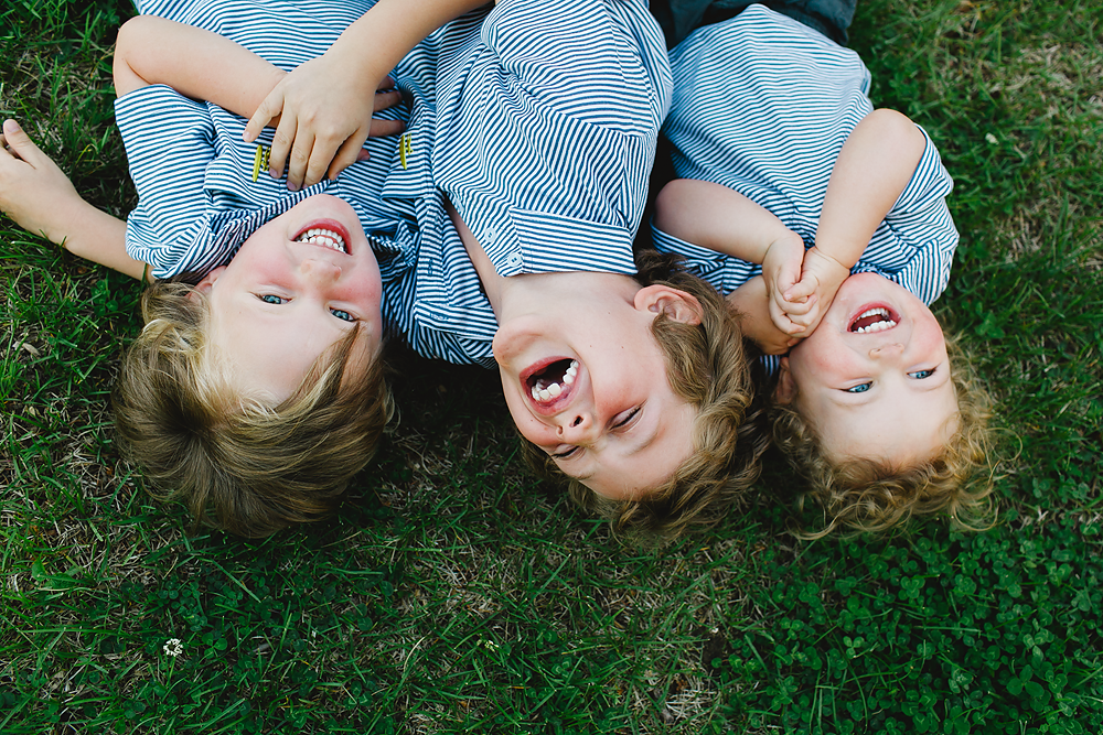 3 kids laughing while laying in the grass by Sara Garcia