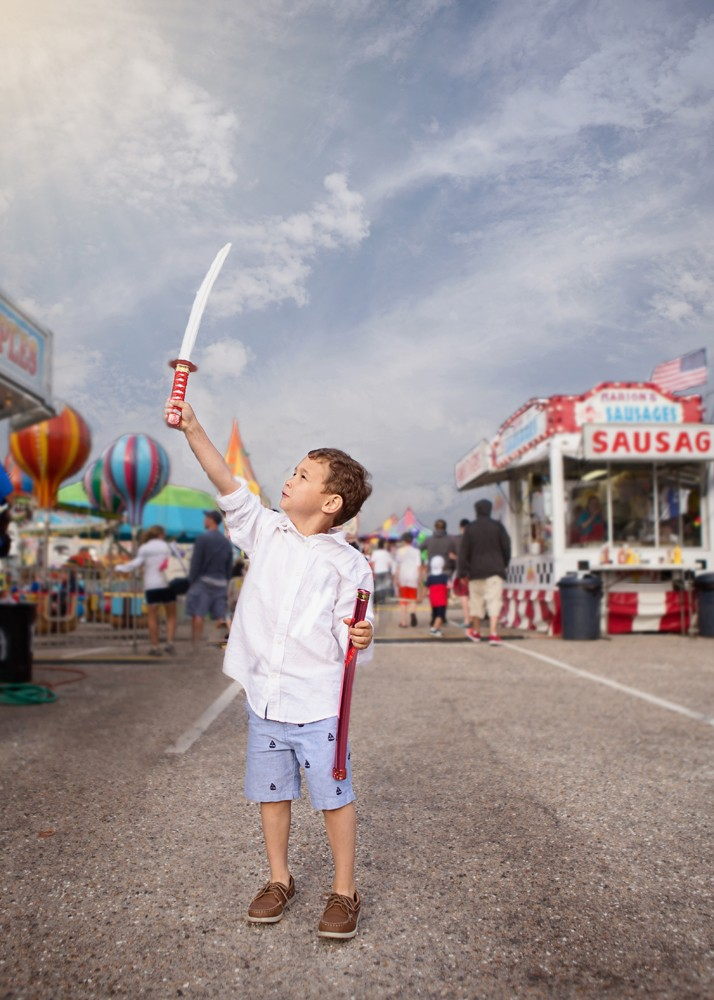 boy holding up a sword at the fair by Christa Paustenbaugh
