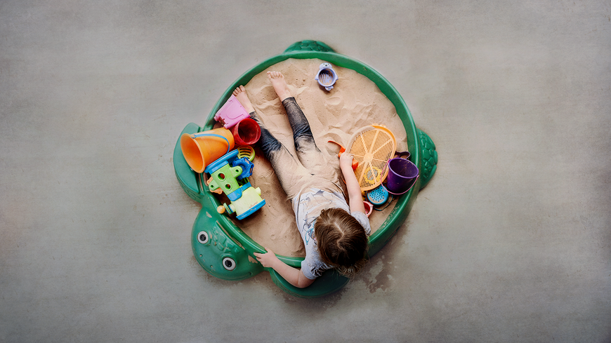 child playing in a turtle sandbox by Kimberly Walla