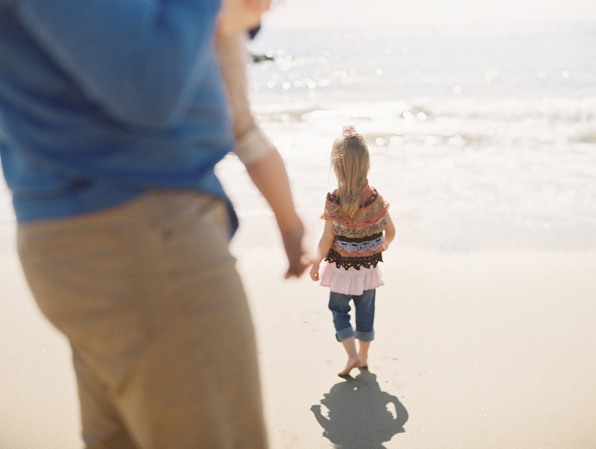 family on beach with little girl at ocean image