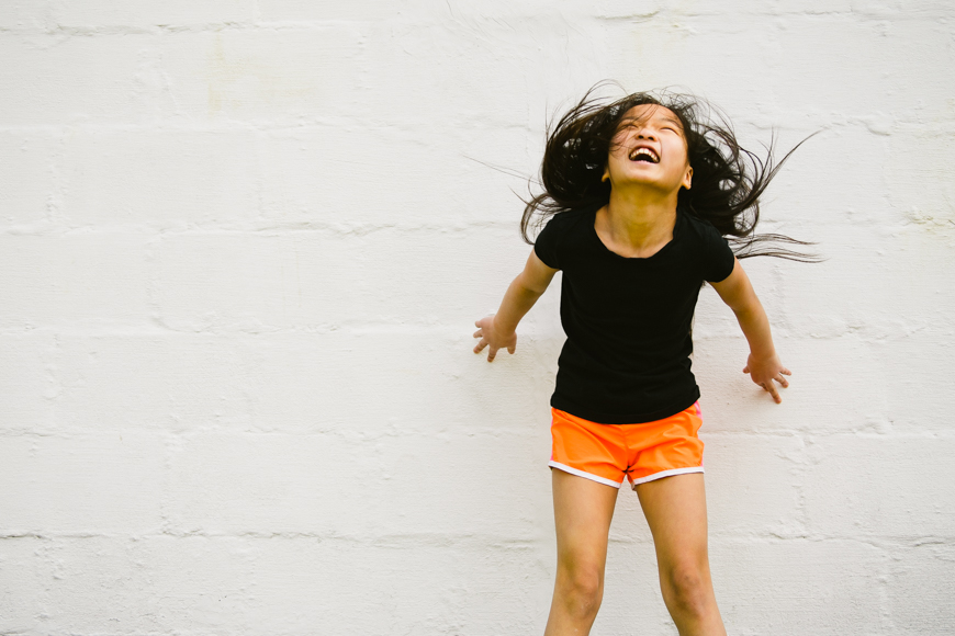 image of girl laughing and jumping against white wall by jane ammon