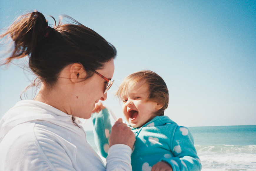 image of mom and little girl in blue jacket at beach by love elizabeth photo