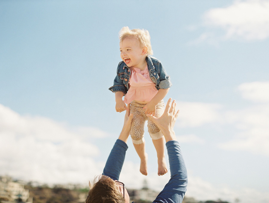 little girl up in air against blue sky by victoria oleary film photographer