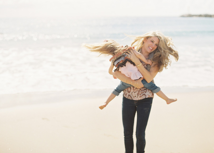 mom swinging girl around on beach image by orange county photographer victoria o'leary