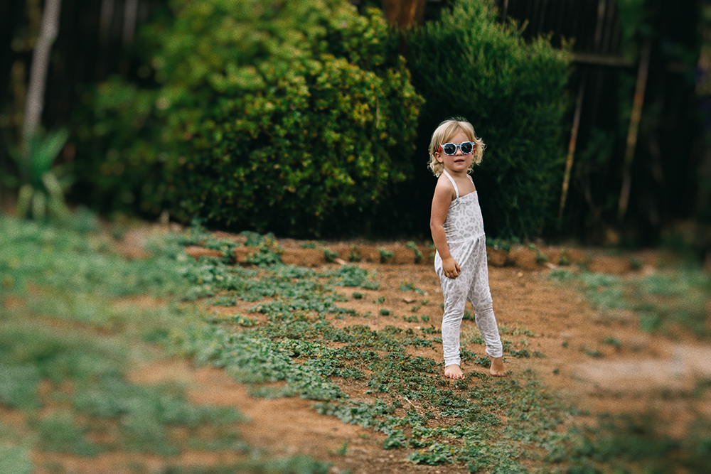photo of a little girl in jumpsuit and glasses by Tarah Sweeney