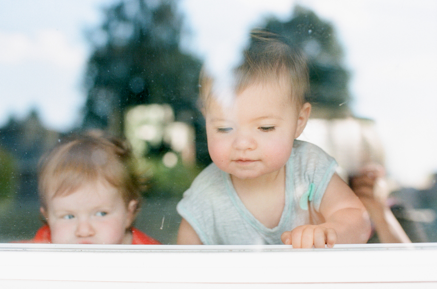 toddler looking out a window pic by Rachael Kruse