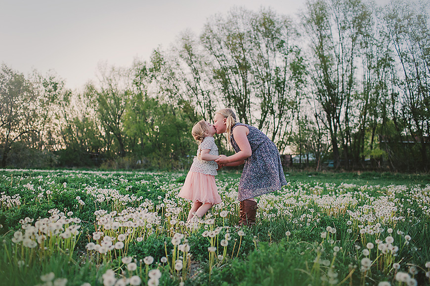 two sisters kissing in field of dandelions by sweet memory garden photo