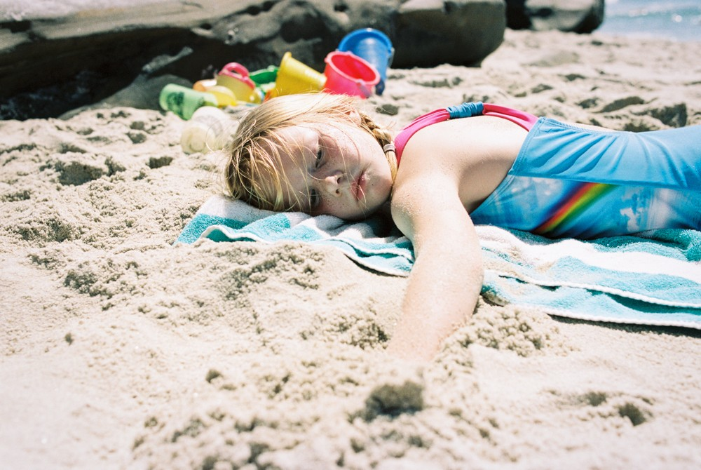 young girl lying on the beach by Posy Quarterman