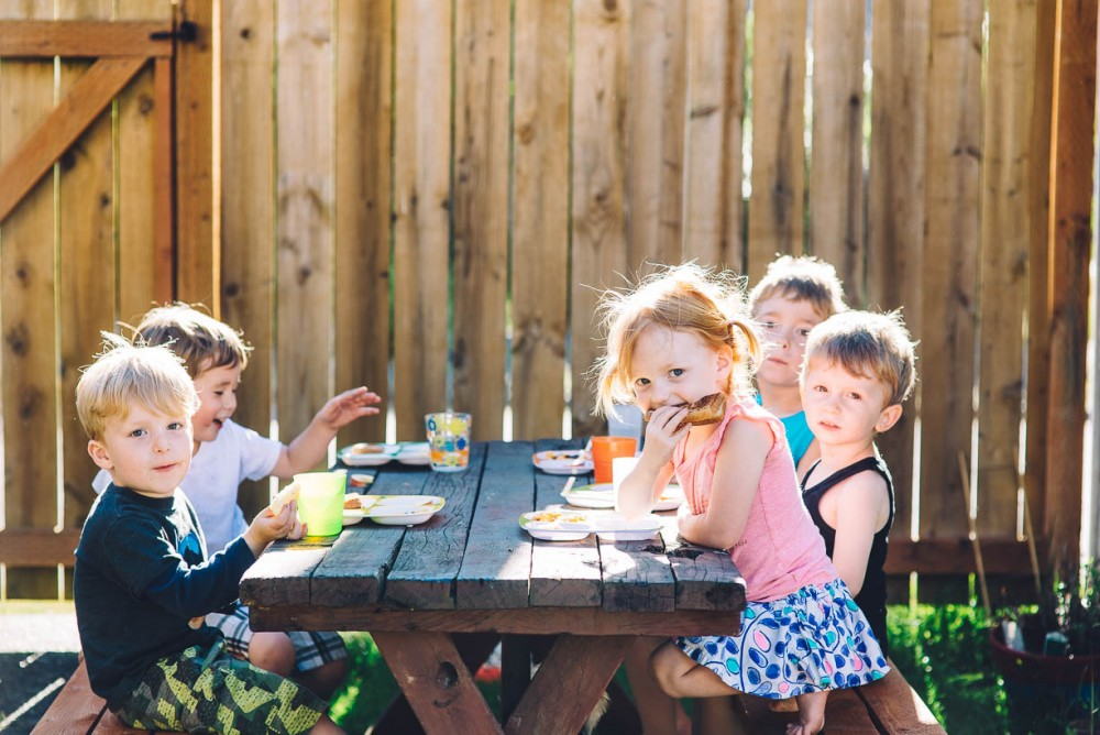 11 image of five young kids eating lunch at a picnic table by devon michelle