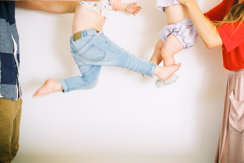 11_image of mom and dad holding young kids in air only bodies visible by samantha kelly