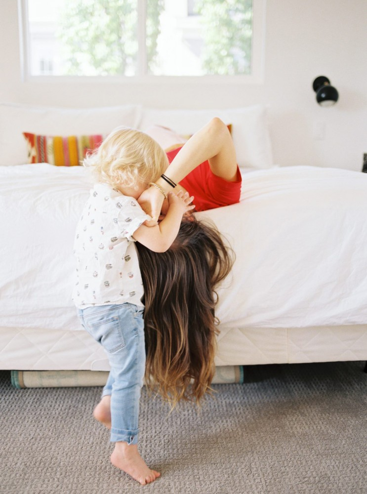 12_image of young boy plays with mother on bed by samantha kelly