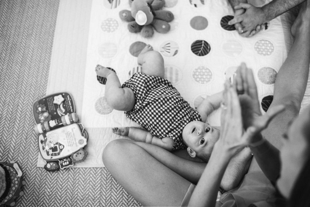 16 image of baby on blanket floor with mom dad toys black white by Lauren MItchell