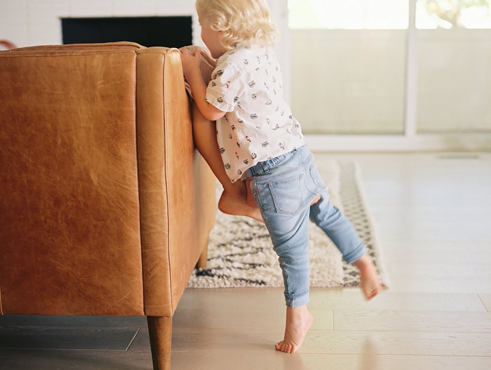 1_photo of young blond toddler playing with person in chari by brooke schultz