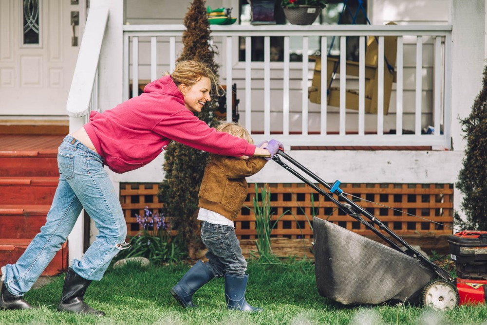 4 image of mother and young son mowing lawn together in front of house by devon michelle
