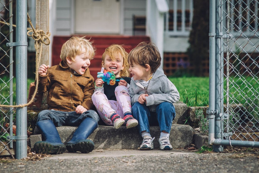 5 image of three young kids sitting on steps in front of house laughing by Devon Michelle
