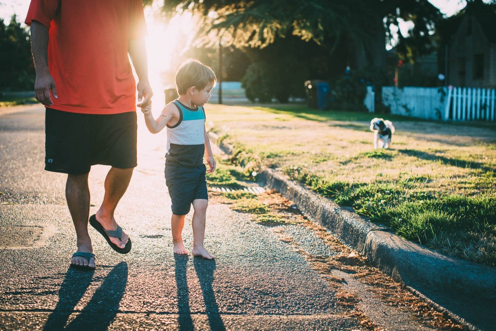 6 picture of father and son walking in street as son sets with dog by devon michelle