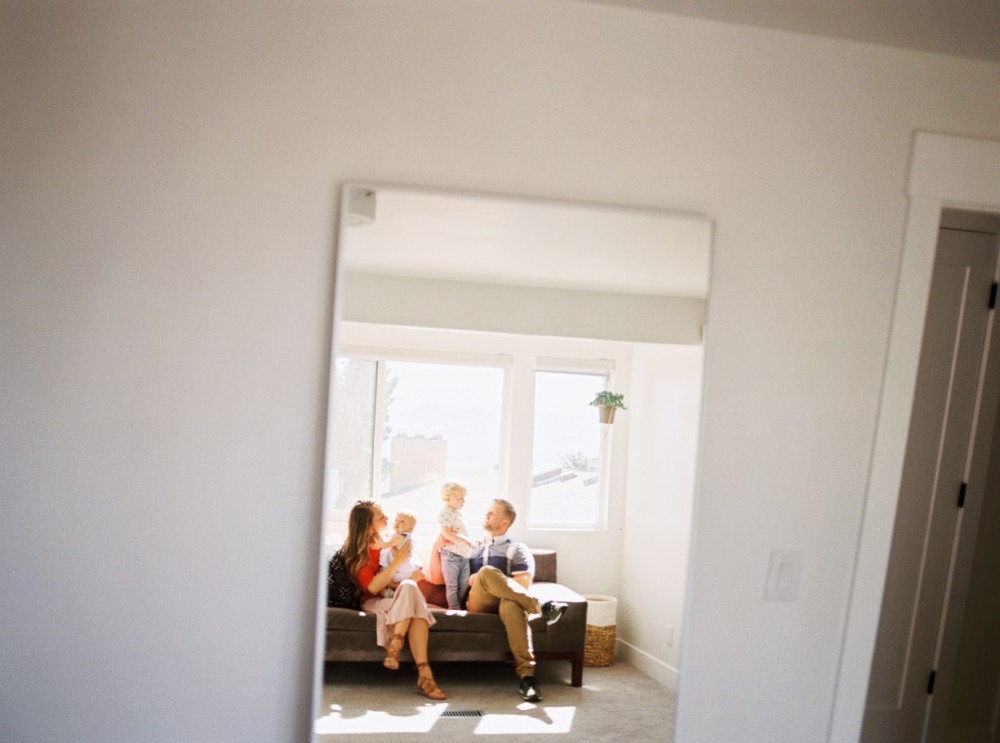9_image of family of four in a mirror reflection sitting on couch by samantha kelly