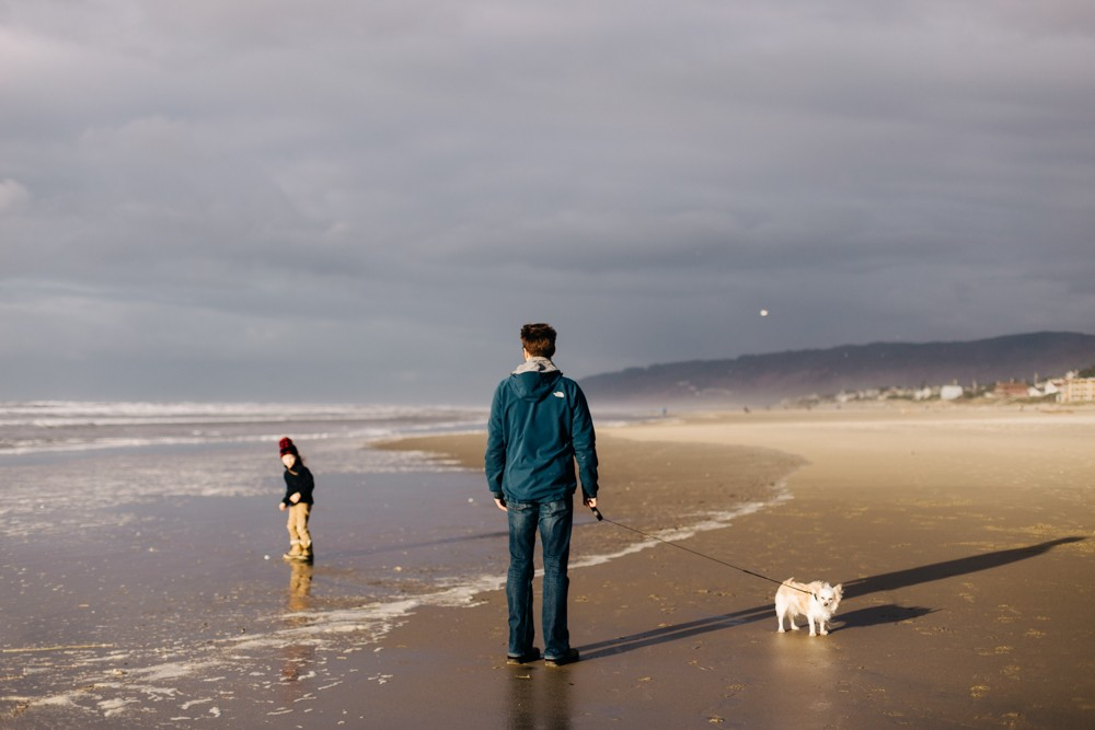 Man with young girl and dog on Oregon coast beach by k dimoff photography