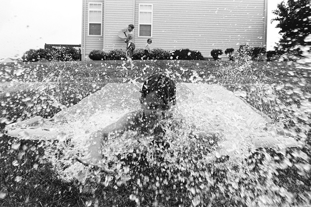 black and white image of boy on slip and slide with water by kiera eve