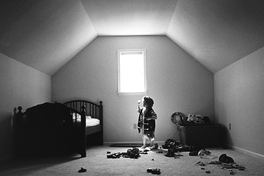 black and white image of little girl in room with toys everywhere by kiera eve