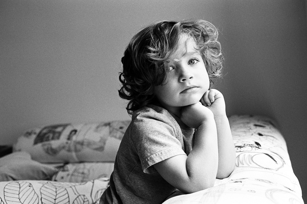 black and white portrait of young boy in room by kiera eve