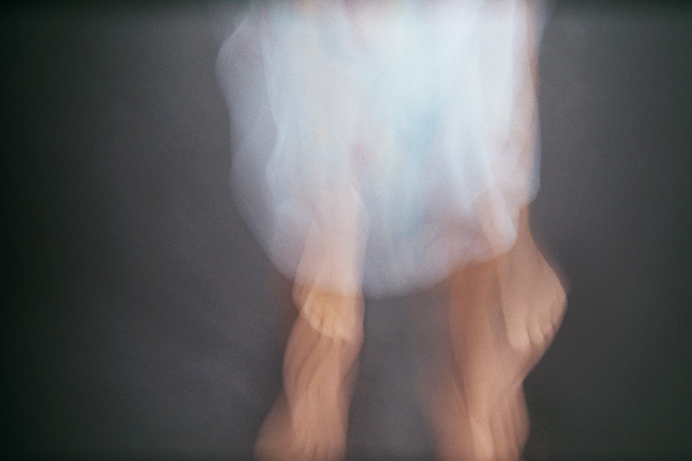 blurry little girl feet in white dress by kiera eve