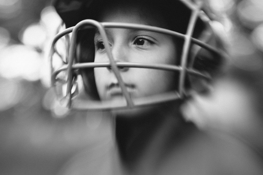 close up photo of young girl in mask playing softball by Lauren Bramlett