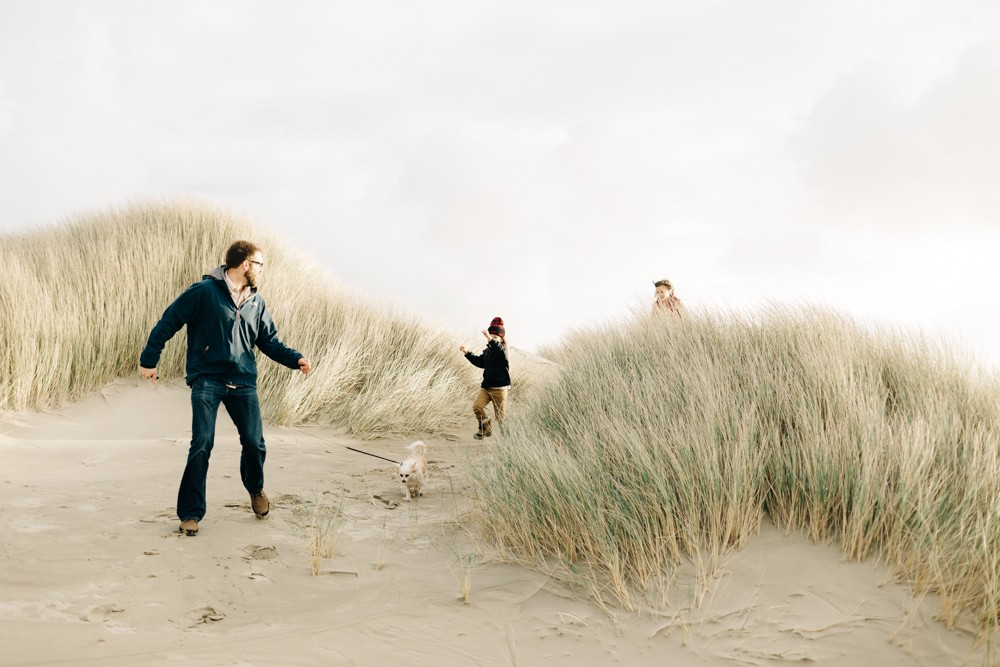 family playing on sand dunes with dog by k dimoff photography