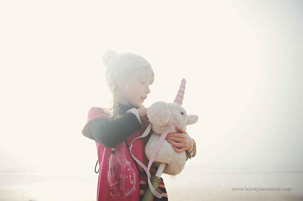 girl on beach in fog holding stuffed unicorn by UAE photographer Kirsty Larmour 09