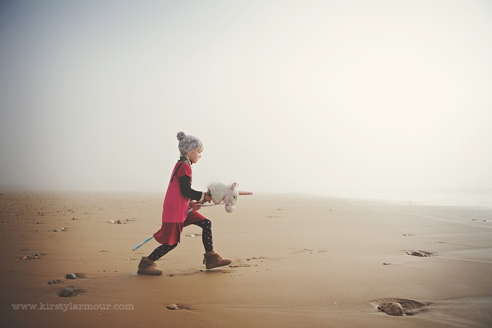 girl on beach in fog riding stuffed unicorn by UAE photographer Kirsty Larmour03