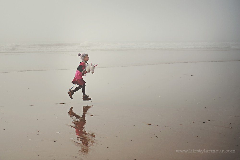 girl on beach in fog riding stuffed unicorn with reflection by UAE photographer Kirsty Larmour04