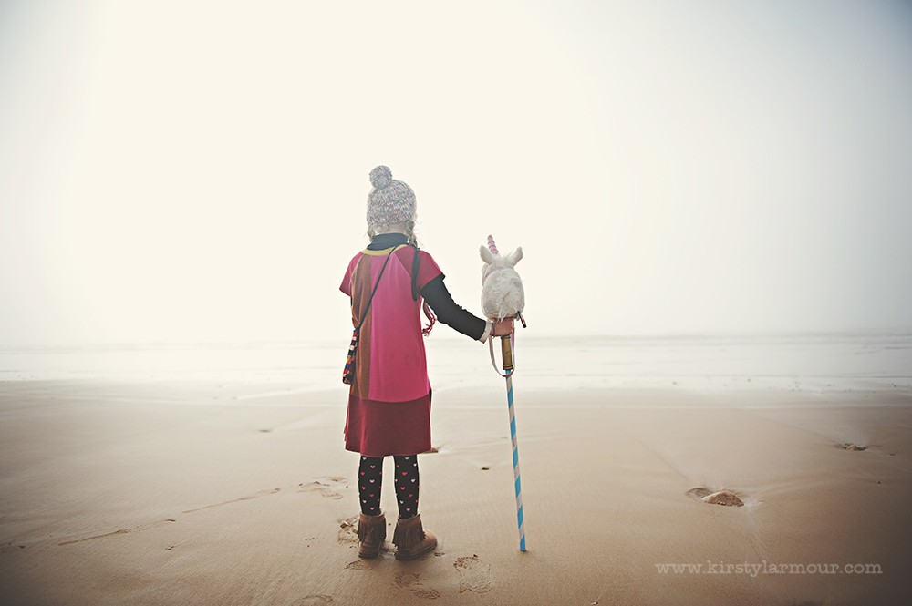 girl on beach in fog with stuffed unicorn by UAE photographer Kirsty Larmour 01
