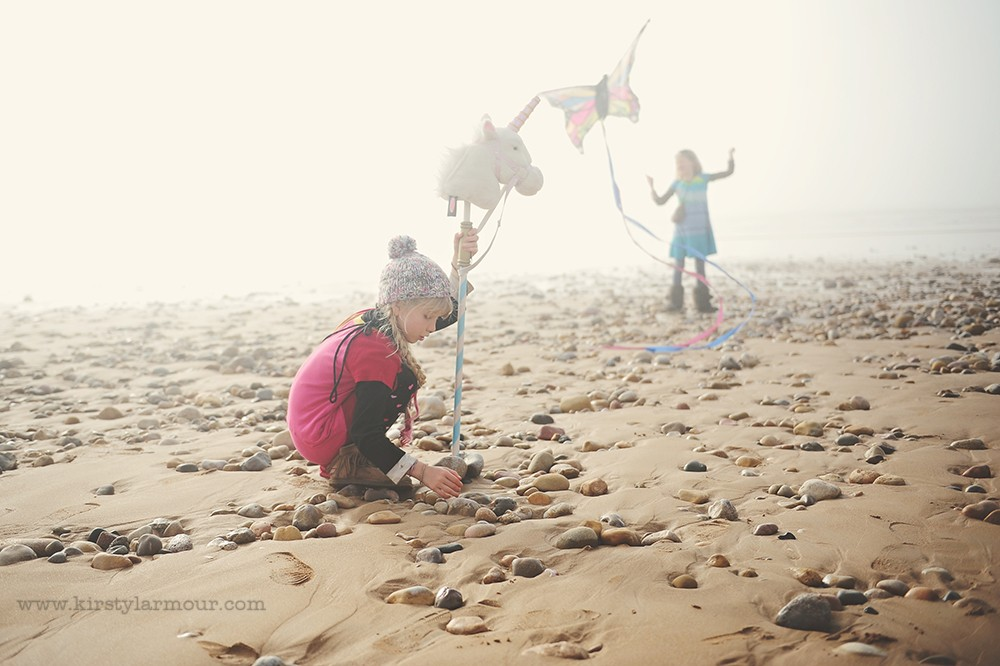 girl on rocky beach in fog with stuffed unicorn by UAE photographer Kirsty Larmour 06