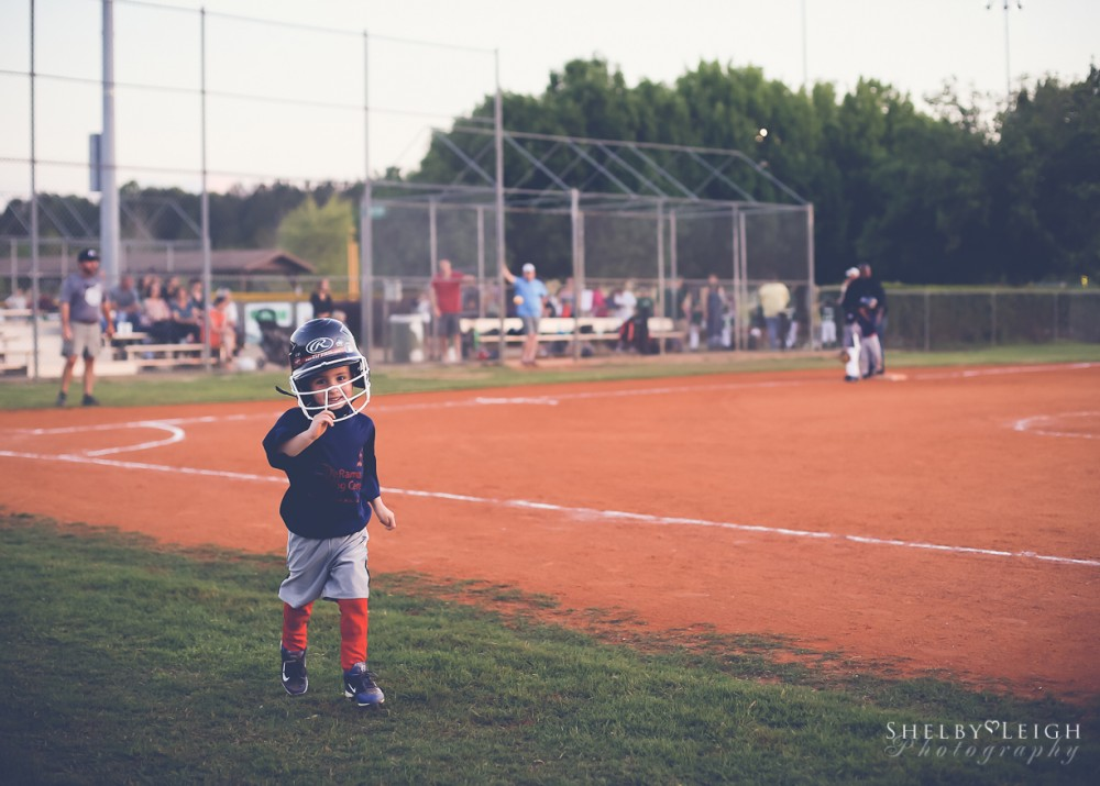 image of young boy walking off baseball field with big helmet by Shelby White