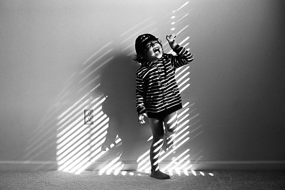 little boy laughing in striped lighting by kiera eve