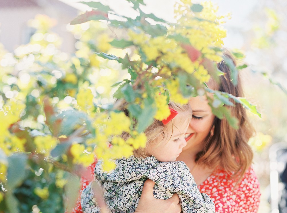 mom and daughter behind yellow flowers image by photographer samantha kelly