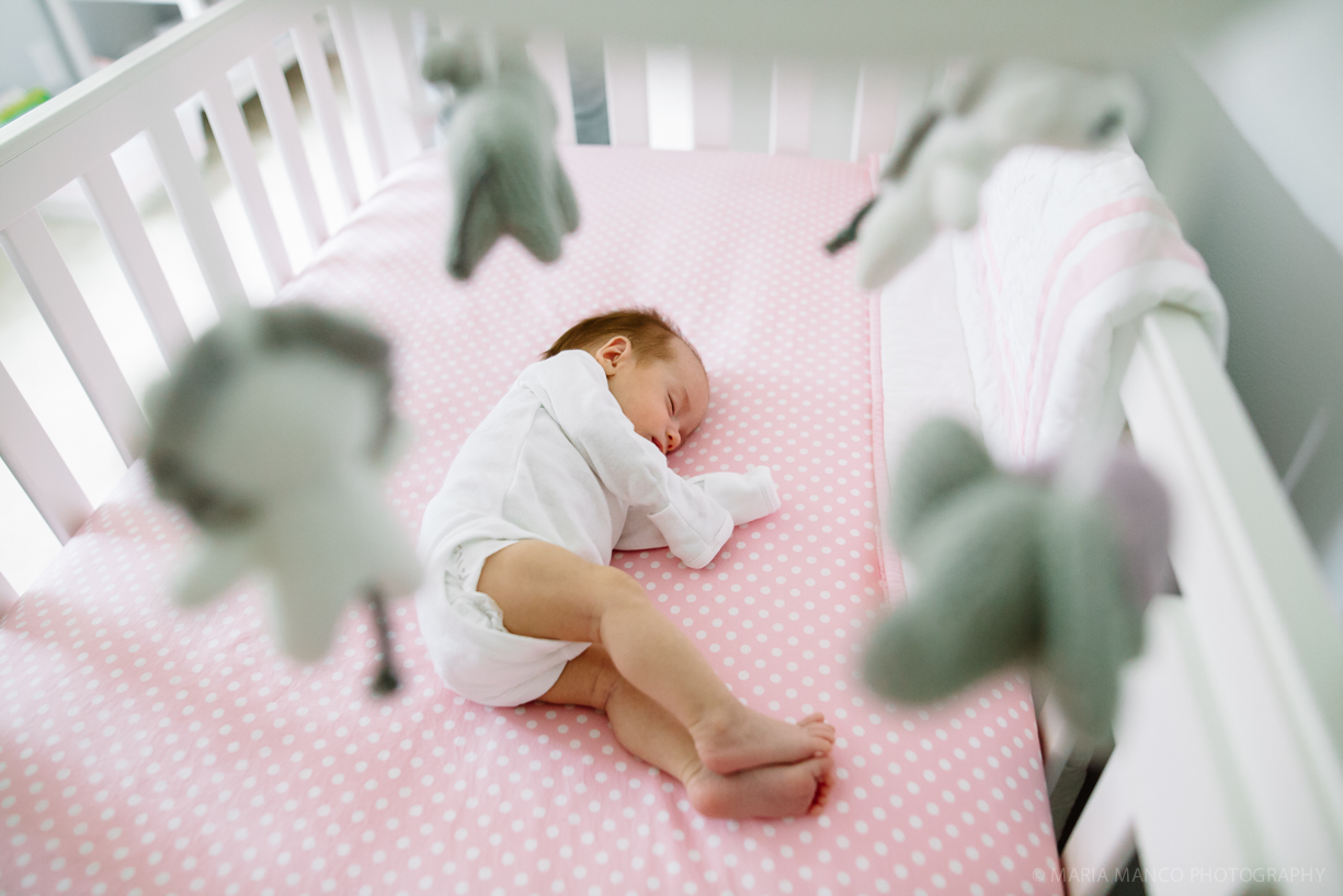 photo of a baby sleeping in her crib with a mobile by Maria Manco