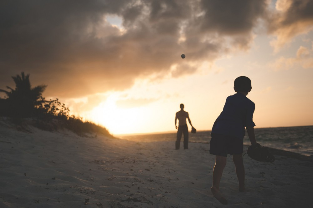 photo of father and son throwing a ball at the beach by Erin Borzellino