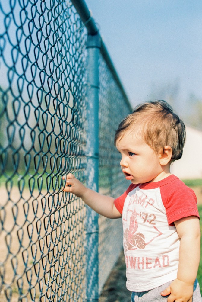 photo of young boy looking through chain link fence by erin holmes