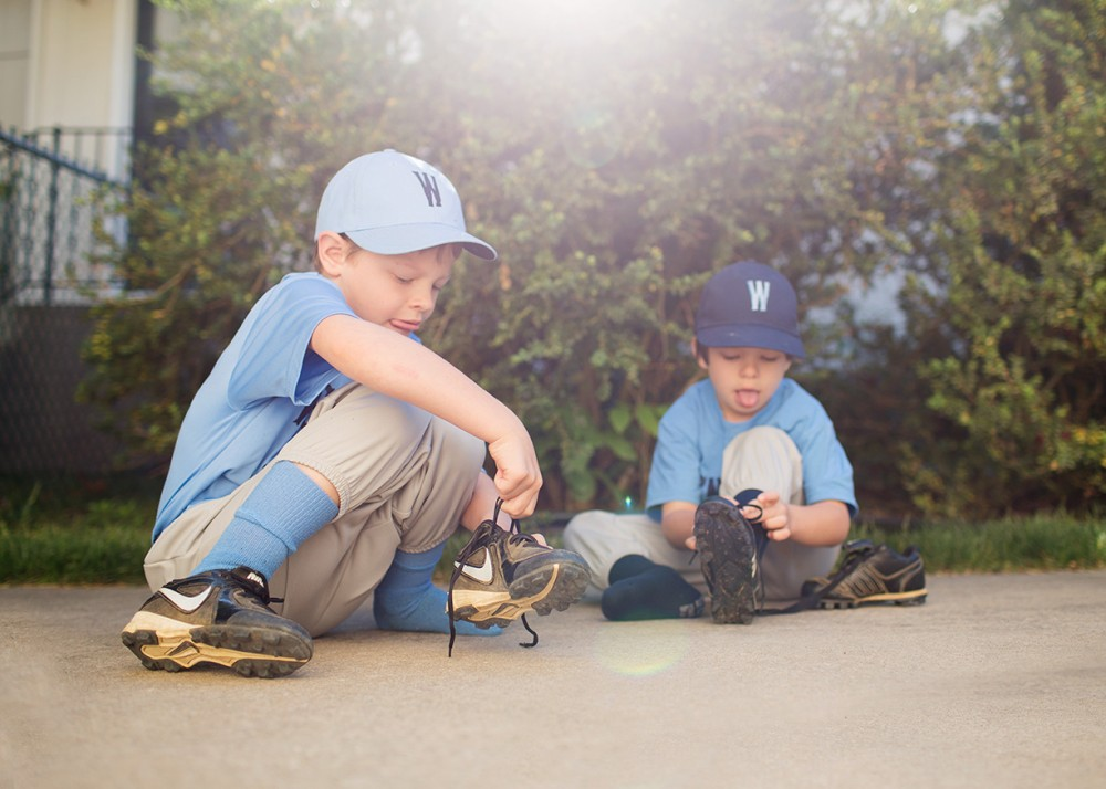 pic of two young boys tying baseball cleats by Rachel McCalley