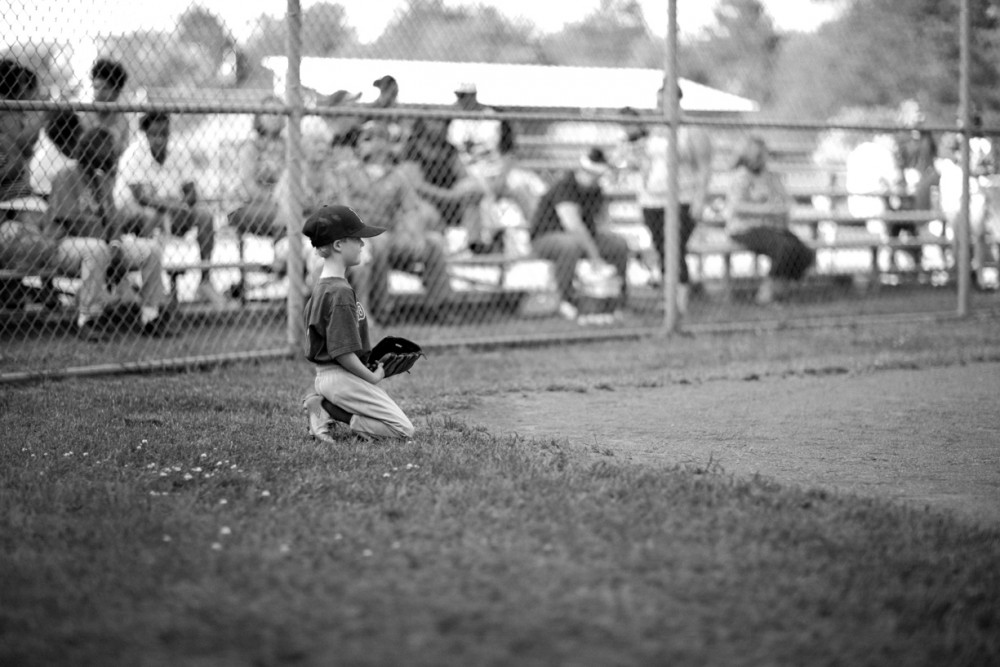 pic of young boy as a catcher with adults in stands by Ashley Waters