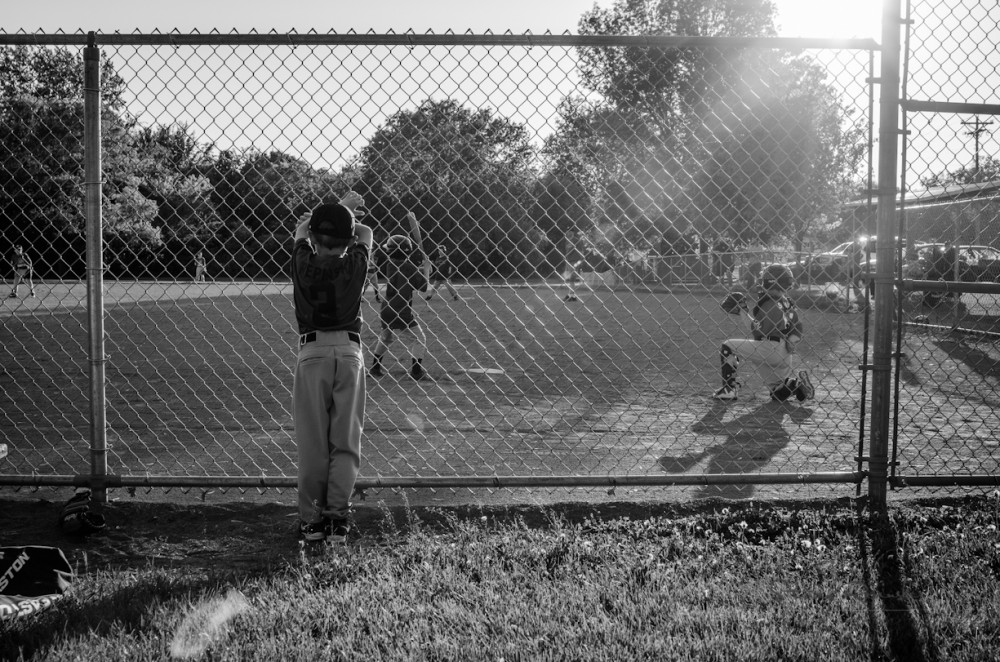 pic of young boy watching baseball game through fence by Stacey Repinski