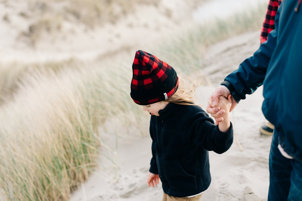 picture of child holding adult's hand on beach by k dimoff photography